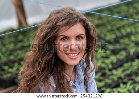 Beautiful young biotechnology woman engineer in uniform in greenhouse with apron and gloves. Greenhouse produce. Food production. - stock photo