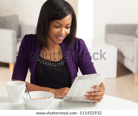 Beautiful young black female sitting at dining room table eating breakfast and drinking coffee. - stock photo