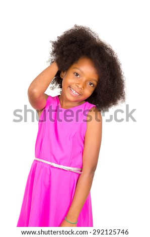 Beautiful young black girl with afro and and pink dress smiling to camera with one hand touching head