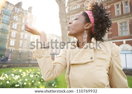 Beautiful young black woman holding the sun in her hand at sunset while visiting London city. - stock photo
