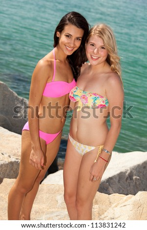 Beautiful young blond and brunette women enjoying the beach. - stock photo