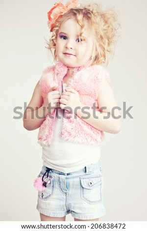 Beautiful young blond female child with curly hair posing in studio