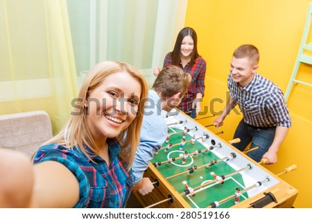 Beautiful young blond girl making a selfie while two boys playing table hockey and a girl cheering them up in a yellow room - stock photo