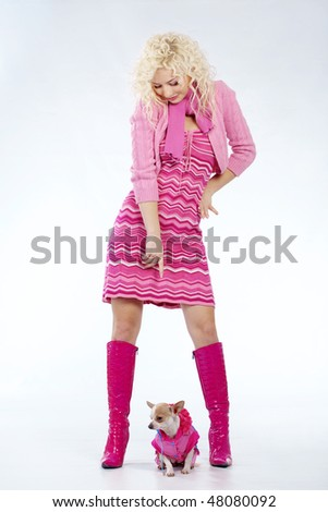 Beautiful young blond girl posing in studio with her small dog - stock photo