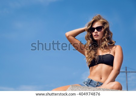 Beautiful young blond girl sitting in shorts and bra on a beach on a background of blue sky
