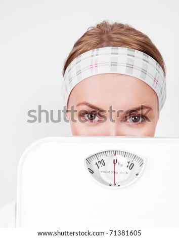 beautiful young blond sporty woman  holding scales - stock photo