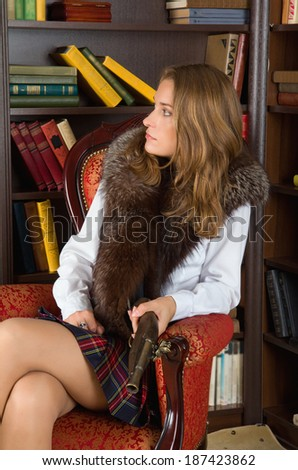 Beautiful young blond  with a gun in her hands - stock photo
