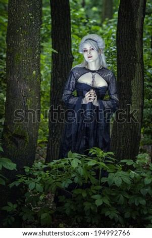Beautiful young blond woman alone in the woods like a ghost. - stock photo