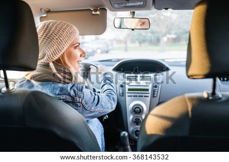 Beautiful young blond woman driving a car - stock photo
