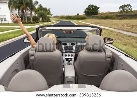 Beautiful young blond woman driving her convertible or cabriolet with her female friend - stock photo