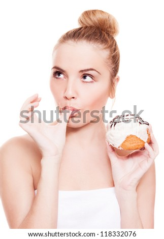 beautiful young blond woman eating a bun and licking fingers, isolated against white background
