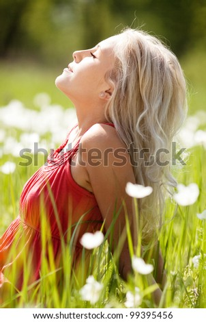 beautiful young blond woman  enjoying the Sun on the  meadow with white flowers  on a warm summer day - stock photo