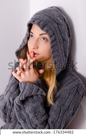 beautiful young blond woman girl in hood praying & looking up - stock photo