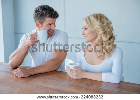 Beautiful young blond woman having coffee with her husband sitting at a wooden table smiling lovingly at him - stock photo