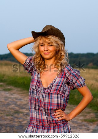Beautiful young blond woman in a cowboy hat and plaided dress standing on a road in the rural area - stock photo