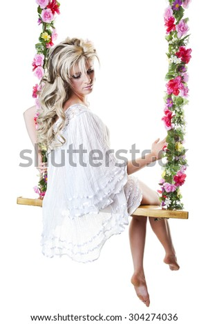 Beautiful young blond woman in a flowing white nightgown, perched on a dreamy floral covered swing.  Shot on white background. - stock photo