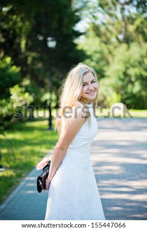 Beautiful young blond woman in a white dress outdoors