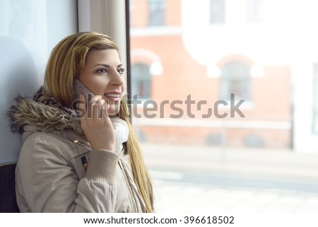 Beautiful young blond woman in coat and long blond hair talking on mobile phone while seated in commuter train during daytime - stock photo