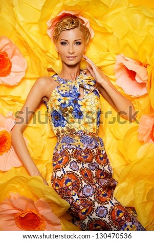 Beautiful young blond woman in colourful dress lying among big yellow flowers - stock photo