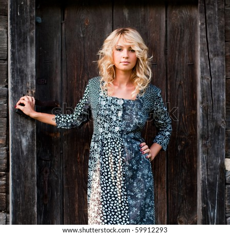 Beautiful young blond woman in the dress near old wooden house - stock photo