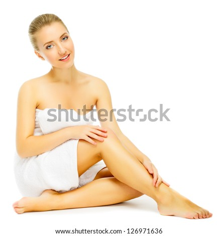 beautiful young blond woman in towel terry sits on  floor, isolated on white