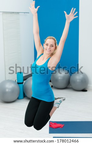 Beautiful young blond woman jumping in a gym with her knees bent and arms extended as she works out doing her exercises