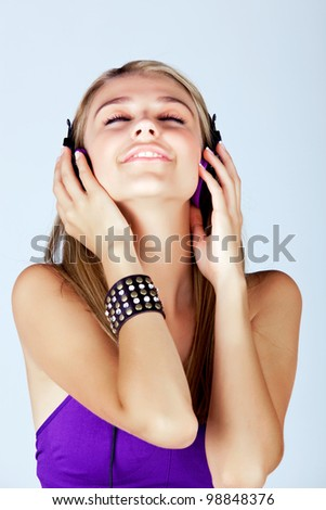 beautiful young blond woman listening to music in headphones wearing purple top and leather fashion cuff on studio background - stock photo