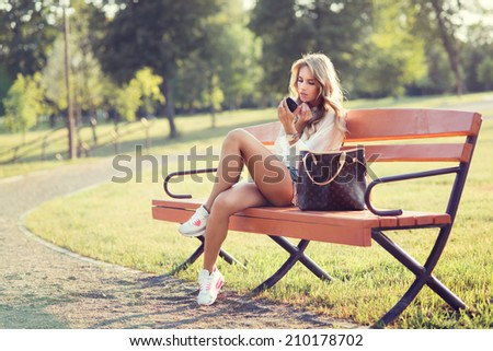 beautiful young blond woman on a bench in the summer - stock photo