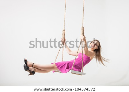 beautiful young blond woman on a swing against white studio background - stock photo