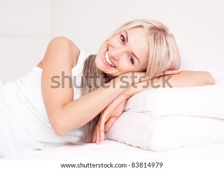 beautiful young blond woman relaxing on the bed at home - stock photo