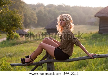 Beautiful young blond woman sitting on a wooden hedge in the sunset light in the rural area - stock photo