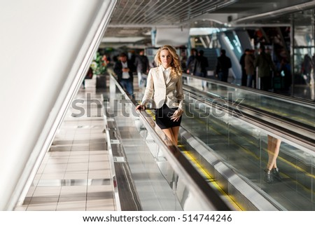Beautiful young blond woman standing on moving walkways indoor