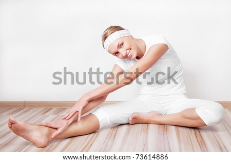 beautiful young blond woman stretching the muscles of her back and legs  at home - stock photo