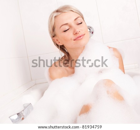beautiful young blond woman taking a relaxing bath with foam - stock photo