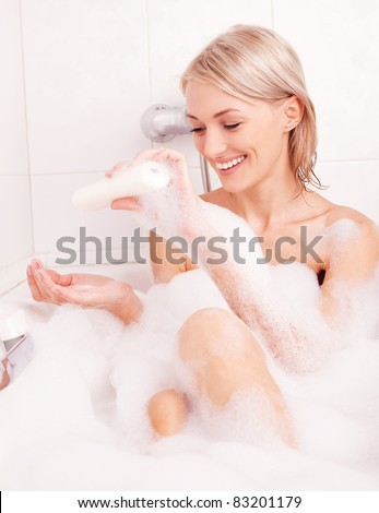 beautiful young blond woman taking a relaxing bath with foam and using cosmetics - stock photo