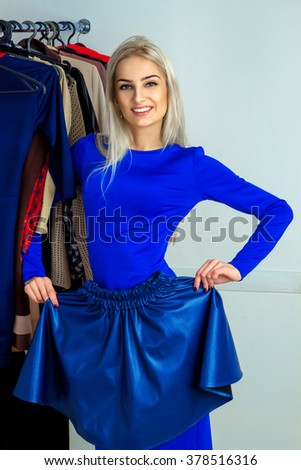 beautiful young blond woman trying on a skirt. Happy young lady with a lot of clothes. Shopping concept. - stock photo