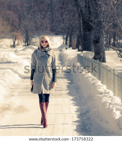 Beautiful young blond woman walking in the park in winter afternoon in coat and red boots, sunglasses. - stock photo
