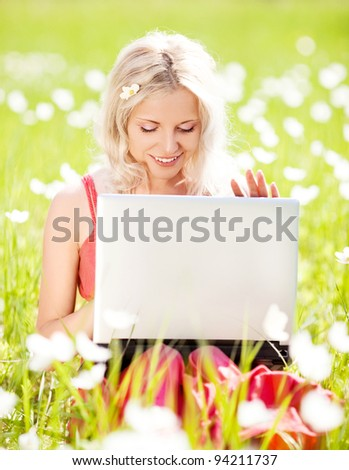 beautiful young blond woman with a laptop  in the park  on a warm summer day - stock photo