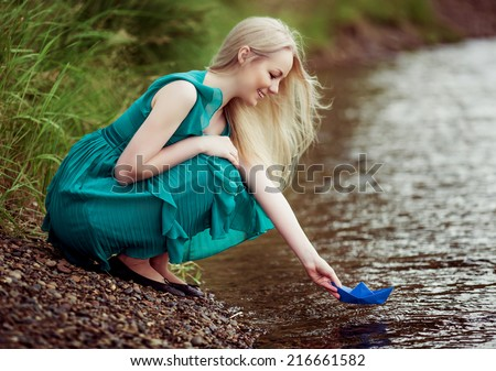 beautiful young blond woman with a paper boat by the lake in summertime - stock photo