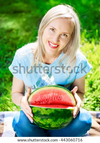 beautiful young blond woman with a water melon in the summer park - stock photo
