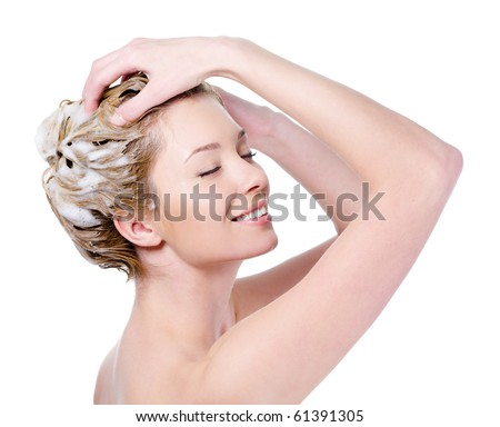 Beautiful young blond woman with attractive smile soaping her head - isolated on white background - stock photo