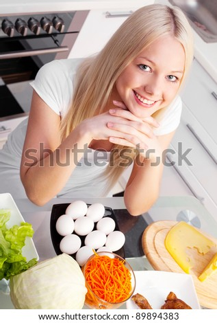 beautiful young blond woman with healthy products in the kitchen at home - stock photo