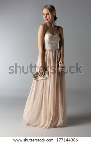 beautiful young blond woman with messy hair in a bun in pastel beige dress on grey studio background - stock photo