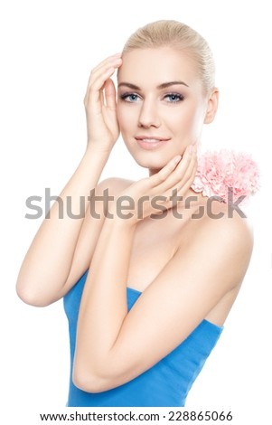 Beautiful young blond woman with pink flower - skin care concept - stock photo