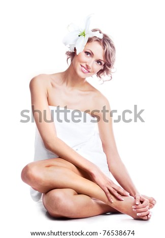 beautiful young blond woman wrapped into the towel  with a lily in her hair - stock photo