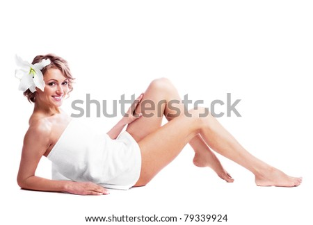 beautiful young blond woman wrapped into the towel  with a lily in her hair, isolated against white background - stock photo