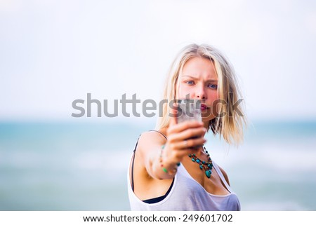 Beautiful young blonde blue eyes woman taking a selfie on smart-phone outdoor at the rocky sea shore. Trendy fashion female model dressed in white top - stock photo