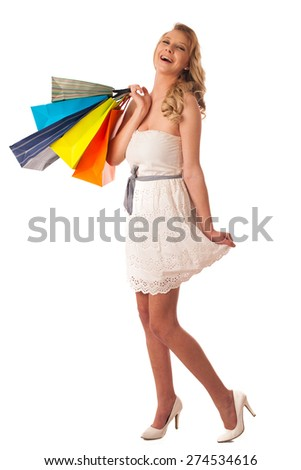 Beautiful young blonde caucasian woman holding vibrant shopping bags in her hands - consumerism