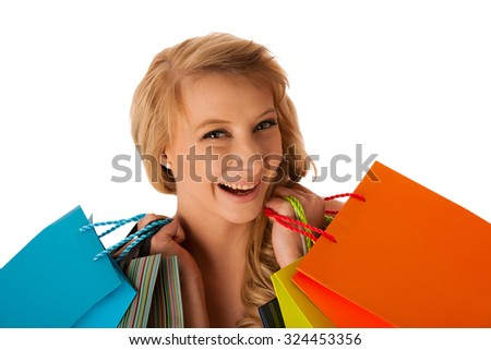 Beautiful young blonde caucasian woman holding vibrant shopping bags in her hands - consumerism - stock photo