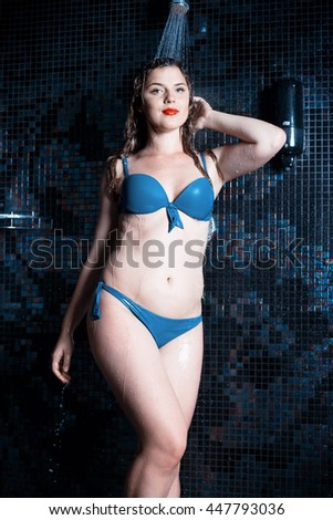 Beautiful young blonde caucasian woman in bikini with waterproof makeup taking shower at spa center, water treatment and body care concept - stock photo
